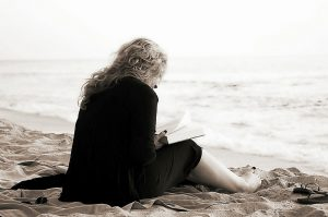 Lady reading on the sand